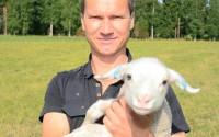 Mathias Hålll med ett veckogammalt lamm på Milågården