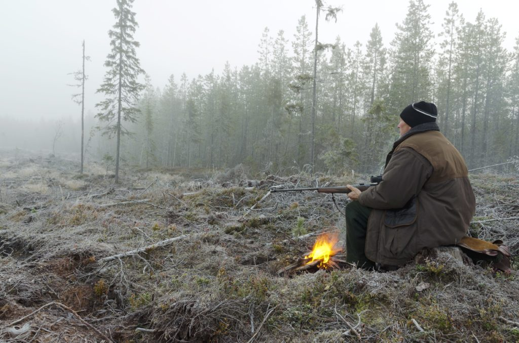 Picture from Left of a Moose hunter sitting on a stump early in the morning with a litle fire in front holding a rifle, picture from the North of Sweden.