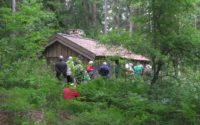 Vandring till Lindstumajas stuga, liten och grå i en glänta i skogen, foto Monika Gustafsson