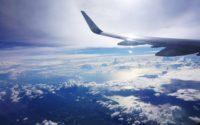 Bild på flygplan uppe i luften, med ett vackert molntäcke som bakgrund